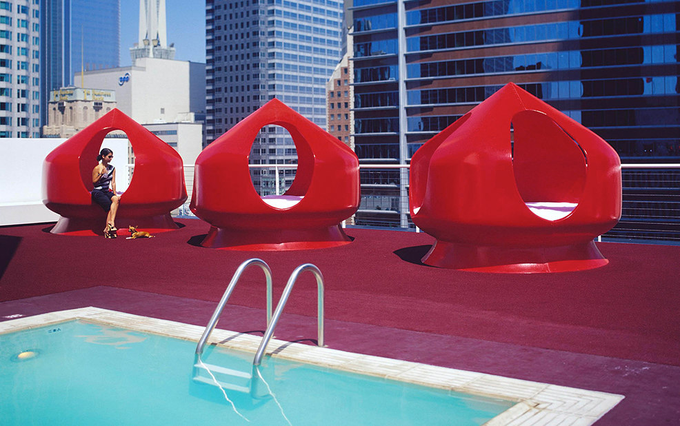 woman on rooftop in red chair by pool – The Standard – point one percent
